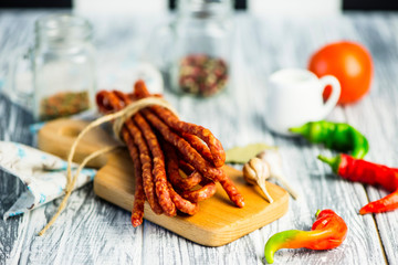 meat sausages with spices and chili peppers on a wooden board