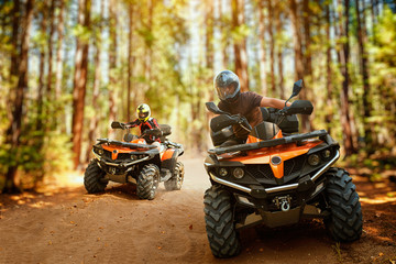 Poster Motorsport Two atv riders, speed race in forest, front view