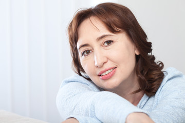Lovely middle-aged brunette woman with a beaming smile sitting on a sofa at home looking at the camera