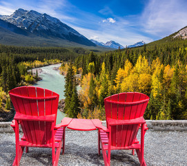 Two red chairs stand by the lake