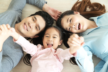 Happy attractive asian family with mom, dad and little cute young daughter or elementary kids holding hands together lying on floor looking at camera on top view feeling enjoy happy time and positive.