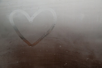 A heart painted on a misted window.Heart on misted glass. Heart on a window background.Heart symbol of love drawn on the glass.