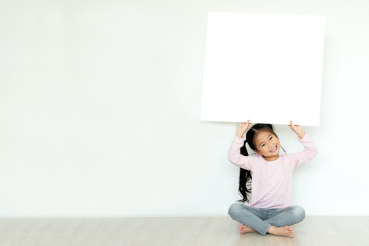 Young little asian girl or kid enjoy holding empty white placard board for media banner, business content presentation, mock up blank sign for message with positive and fun in creative design concept.