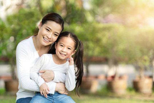 Portrait of young happy asian mother and little cute daughter smiling, sitting and looking at camera at outdoor public nature park with copy space in family bonding and casual relax lifestyle concept.