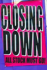 Closing Down, All Stock Must Go - sign in shop window. Black and white writing on a pink sign against purple background.