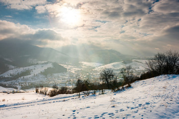 magical winter countryside. sun ray through the cloudy sky. snowy hill and leafless trees. village down in the valley