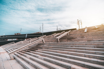 Wide-angle view of a wide contemporary stairway with multiple stone rails for skating; a huge broad modern staircase in urban settings, Forum district of Barcelona, Spain