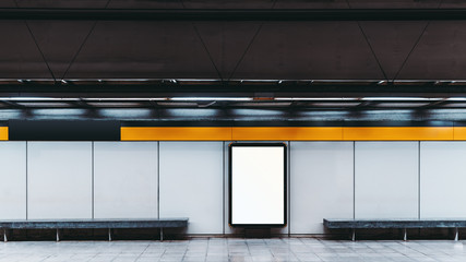 Mockup of a blank white advertising urban billboard indoors in subway hall; empty information banner placeholder template on the metro or railroad station with two concrete benches on the sides