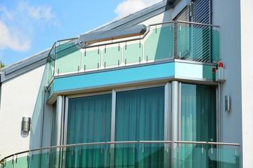 Grün verglaster Edelstahlbalkon mit integriertem Edelstahl-Blumenkasten und Edelstahl-Glas-Sockel sowie Alarmanlage für Brandschutz