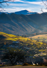 lovely countryside scenery in afternoon. village down in the valley. distant mountain with snowy top. green grass on rural hills