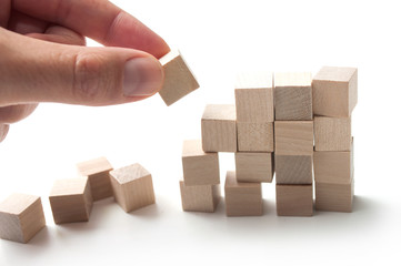 closeup of hand with wooden brick of construction game on white background