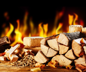 Stacked dried logs in front of a burning fire
