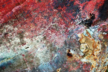 Abstract textured background of old decaying wooden boat panels with mostly red and black peeling paint.