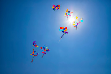 The multi colored helium balloons flying In the blue sky. the concept of a wedding, celebration, anniversary, entertainment