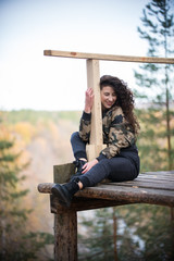 Young woman sitting on a platform on a background of the forest, smiling, hugging a rail