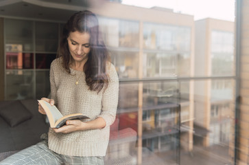 Adult woman with book standing close to sofa and window