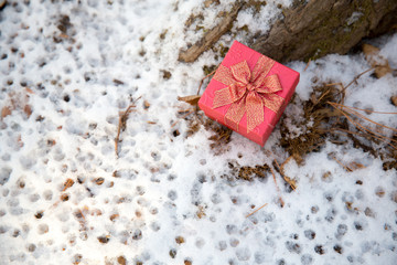 Christmas gift in red box on the snow background, gift box with its lid propped at an angle in front to display the beautiful shiny with falling winter snowflakes and copyspace for your insert text.