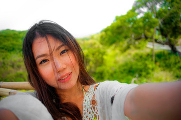 young beautiful and happy Asian Korean woman taking self portrait selfie picture with mobile phone for uploading to internet social media enjoying holidays