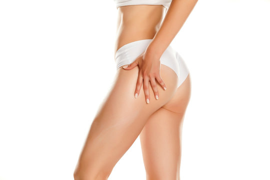 Young woman applying cream on her buttocks on white background