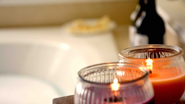 Candles, wine and cheese by the bathtub