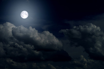 The full moon between the clouds in the night sky
