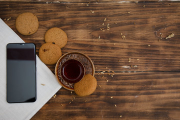 Smart phone tablet and biscuits with tea on the table