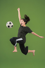 Forward to the victory.The young woman as soccer football player jumping and holding the ball at studio on green background. Football fan and world championship concept. Human emotions concepts