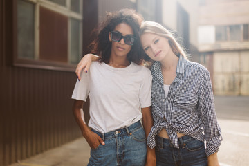 Young african american woman with dark curly hair in sunglasses and T-shirt and pretty woman with blond hair in shirt dreamily looking in camera while spending time together