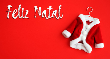 Feliz Natal (in Portuguese: Merry Christmas) text and Santa Claus (Saint Nicholas) coat suit costume with white clothing cuffs isolated on vivid red background. Concept photo for Christmas holidays.