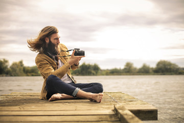 Handsome man sitting on a pier, taking pictures with his camera
