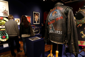 Visitors walk past items related to the career and life of French singer Johnny Hallyday on display before an auction at Drouot auction house in Paris