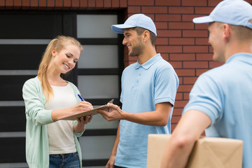 Two friendly couriers and girl signing a form