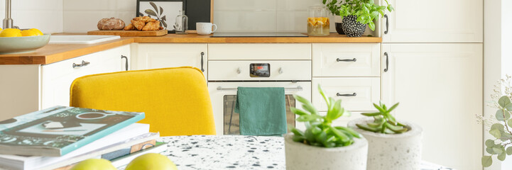 Closeup of stylish kitchen interior design with white cabinets, oven and yellow chair, panoramic view, real photo