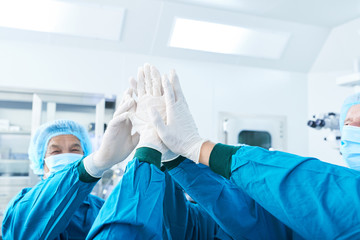 Crop surgeons in gloves giving high five to each other before performing surgery in modern hospital