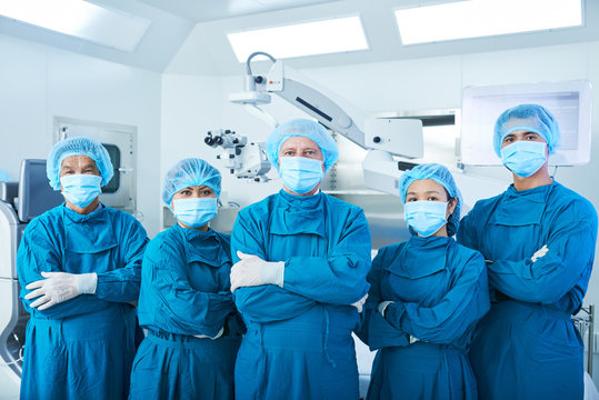 Asian surgical team in masks and uniform keeping arms crossed and looking at camera while standing in operating theatre together