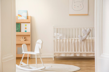 Open door to scandinavian kid's bedroom with white rocking horse, crib with bedding and poster on the wall, real photo