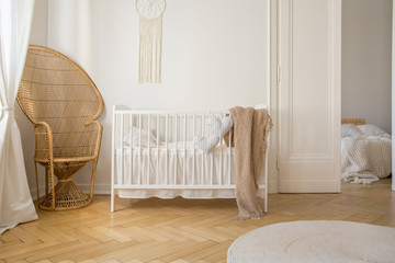 Wicker peacock chair next to white bedding in stylish kid bedroom, real photo