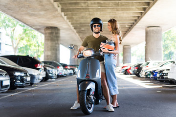 Happy couple with motor scooter at underpass