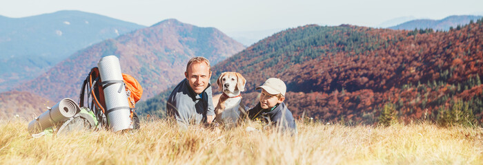 Poster Camping Father and son backpackers hikers rest on mountain hill with their beagle dog