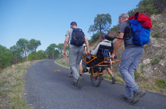 randonnée solidaire avec des gens qui aident des handicapés avec une joelette sur route