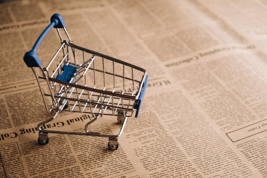 Empty shopping cart on newspaper background with copy space for text, Shoping online concept.