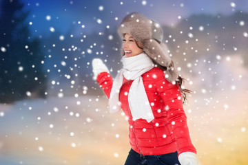 people, season and leisure concept - happy woman in winter fur hat having fun outdoors over evening background and snow