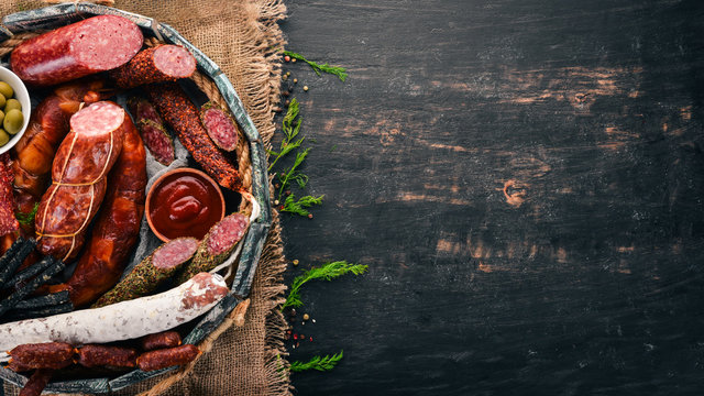 Assortment of sausages and snacks in a wooden box. Sausage Fuet, salami, paperoni. On a black background. Top view. Free space for your text.