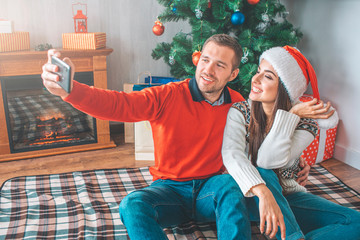 Young man sit on blanket with woman and takes selfie. He embrace her. She poses and smiles. Young woman holds part of her Christams hat. They look happy.