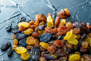 Assortment of Raisins, yellow, blue, black, golden raisin on dark background. Healthy snack, dietary product for good life. Food background and texture, Vega Food. Close-up image. Macro.