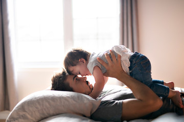 Young father with child girl on bed at home