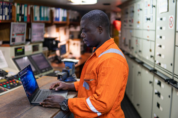 African marine engineer officer in engine control room ECR. Seamen's work. He works at the computer