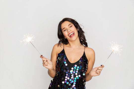 celebration, fun and holidays concept - happy young woman in sequin dress with sparklers at party