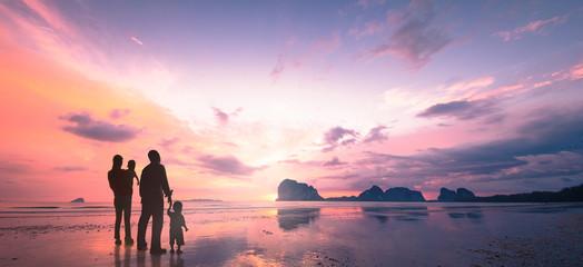 International migrants day concept: Father, mother and two son over beach sunset background