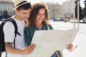 Tourist couple traveling and using map, exploring city.